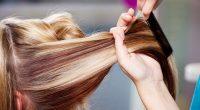 Hair Dresser Combing Client's Hair In Salon